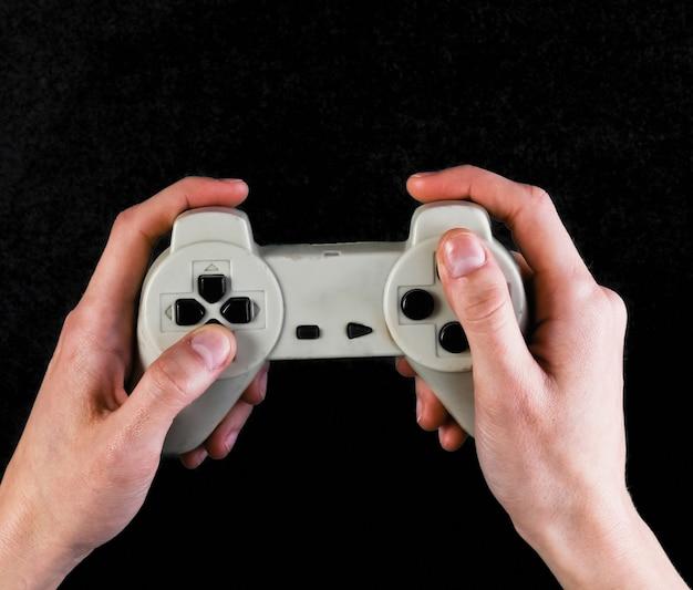 Le mani femminili tengono il gamepad sul nero