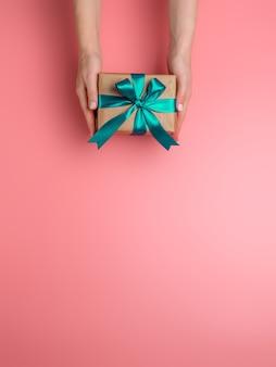Le mani femminili tengono la confezione regalo su sfondo rosa, copia spazio verso il basso. la ragazza caucasica passa il contenitore di regalo della tenuta in carta da imballaggio del mestiere con il nastro di raso verde.