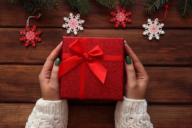 Le mani femminili tengono una confezione regalo su un tavolo di legno con rami e decorazioni di albero di natale
