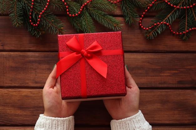 Le mani femminili tengono una confezione regalo su un tavolo di legno con rami di albero di natale