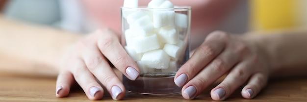 Le mani femminili tengono il vetro con lo zucchero