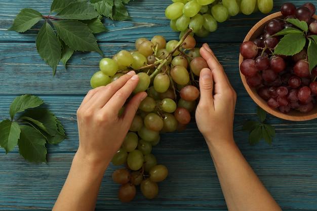 Le mani femminili tengono l'uva su fondo di legno