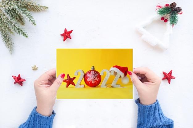 Le mani femminili tengono un biglietto di auguri di natale sullo sfondo di un tavolo bianco con decorazioni natalizie.