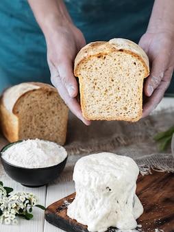 Le mani femminili tengono pane appena sfornato mezzo cotto, lievito naturale e ingredienti da forno su un tavolo di legno bianco