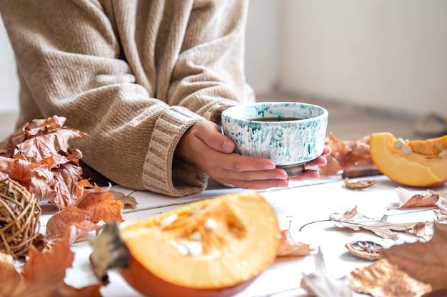 Le mani femminili tengono una tazza di ceramica fatta a mano con una bevanda calda sull'arredamento di autunno.