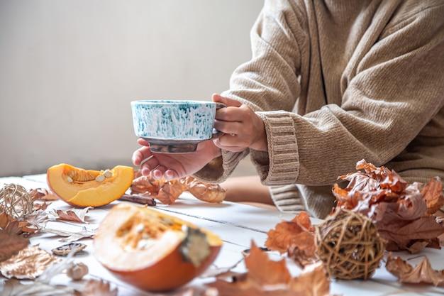 Le mani femminili tengono una tazza in ceramica fatta a mano con una bevanda calda sullo sfondo della decorazione autunnale.