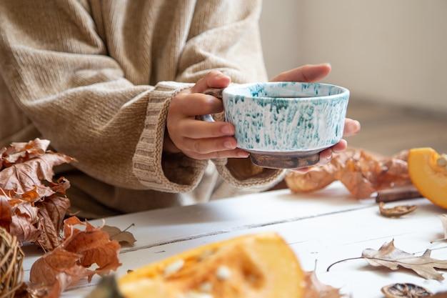 Le mani femminili tengono una tazza in ceramica fatta a mano con una bevanda calda su uno sfondo sfocato.