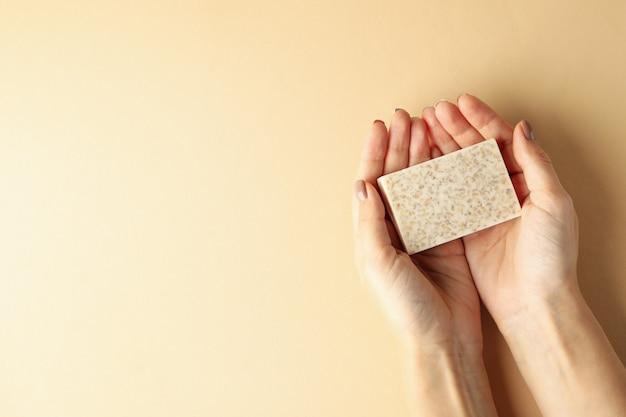 Le mani femminili tengono il sapone fatto a mano su fondo beige