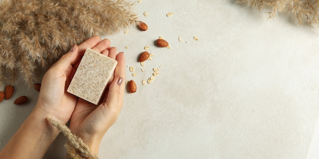 Le mani femminili tengono il sapone fatto a mano su fondo decorato