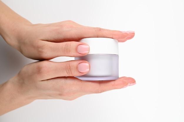 Le mani femminili tengono un vasetto di crema, su un fondo isolato.