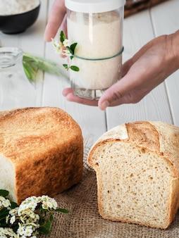 Le mani femminili tengono un vaso con lievito naturale attivo nelle loro mani vicino al pane di frumento