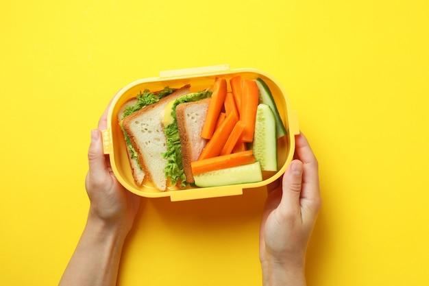 Le mani femminili tengono la scatola del pranzo su sfondo giallo