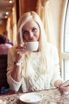 Le mani femminili tengono una tazza di cioccolata calda. una giovane donna è seduta in un accogliente bar. la ragazza sta bevendo il cacao. inverno. accogliente autunno.