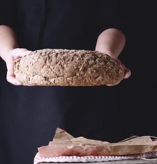 Le mani femminili tengono il pane di segale al forno ovale con i semi di zucca Foto Premium