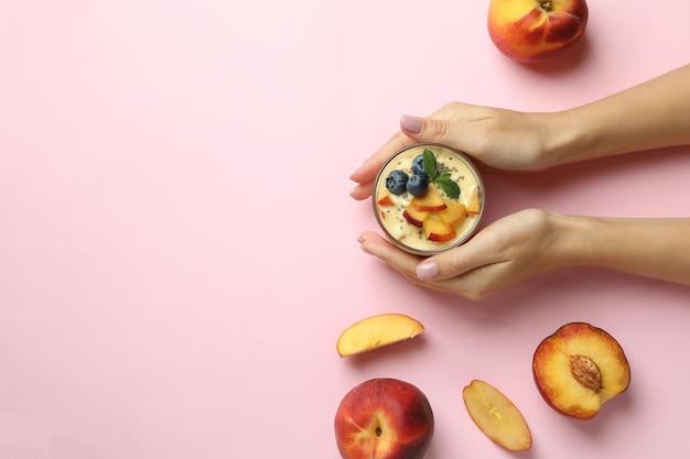 Le mani femminili tengono lo yogurt alla pesca su sfondo rosa