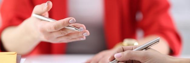 Le mani femminili tengono penne e documenti sopra il tavolo di lavoro. corsi di formazione e formazione per lo sviluppo del concetto di business