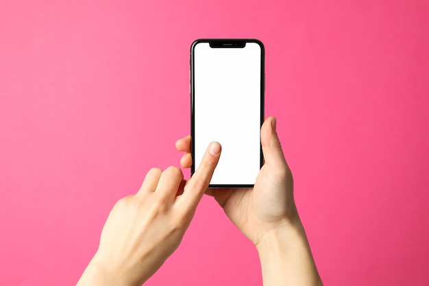 Le mani femminili tengono il telefono su fondo rosa. schermo vuoto