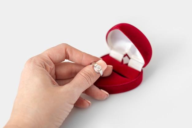 Le mani femminili tengono la scatola rossa con l'anello di diamante su fondo bianco