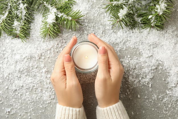 Mani femminili tengono candela profumata su sfondo grigio con neve e rami di pino