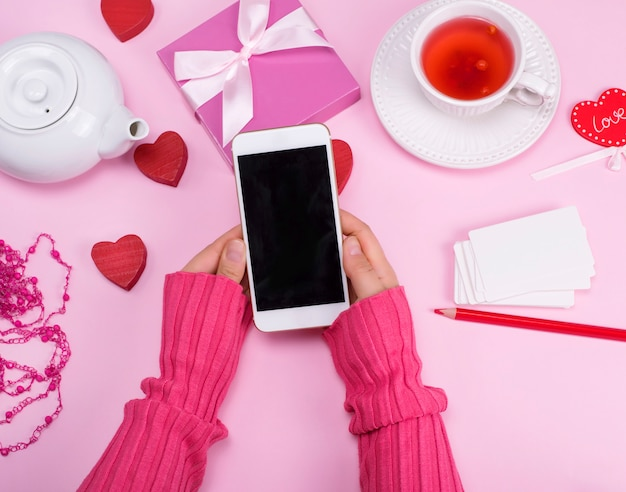Le mani femminili tengono uno smartphone con uno schermo in bianco nero
