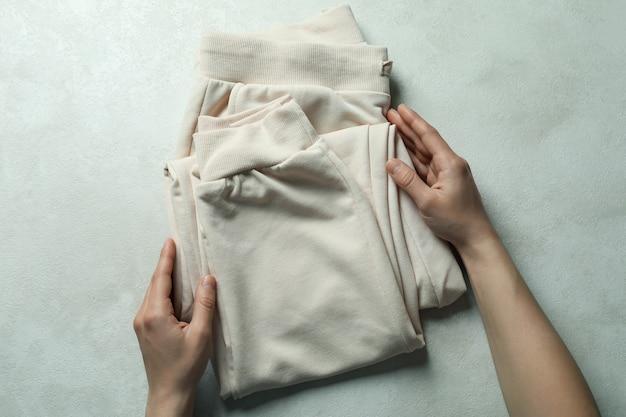 Le mani femminili tengono i pantaloni della tuta su bianco