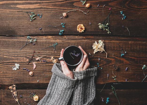 Le mani femminili tengono il tè accanto a ramoscelli secchi su un tavolo di legno