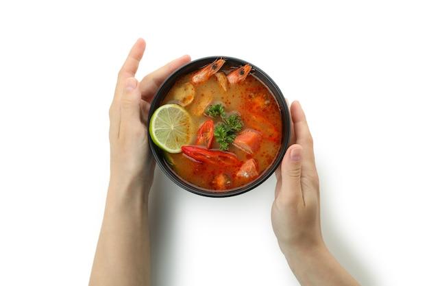 Le mani femminili tengono la zuppa tom yum, isolata su sfondo bianco
