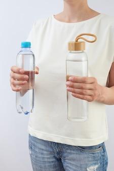 Le mani femminili tengono due bottiglie di plastica e vetro con acqua fresca pulita contro un tavolo grigio chiaro, copia dello spazio. concetto di rifiuti zero. utilizzando una bottiglia di vetro riutilizzabile invece di plastica monouso.