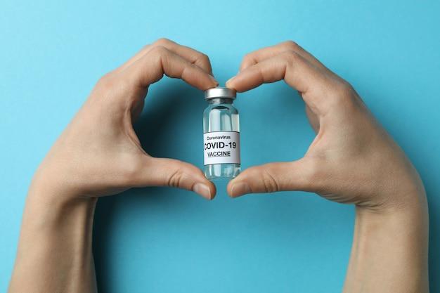 Le mani femminili tengono la fiala di vaccino covid - 19 sul tavolo blu