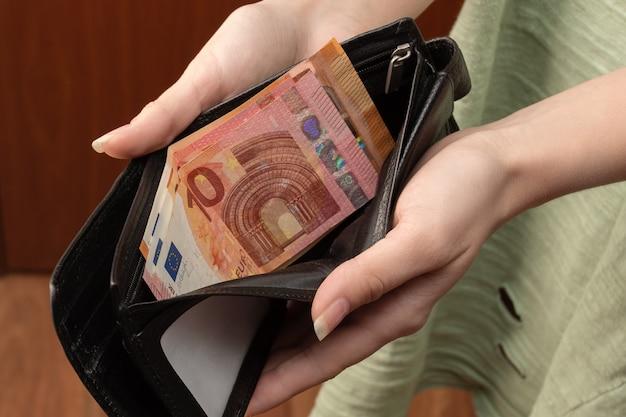 Le mani femminili tengono un portafoglio con contanti