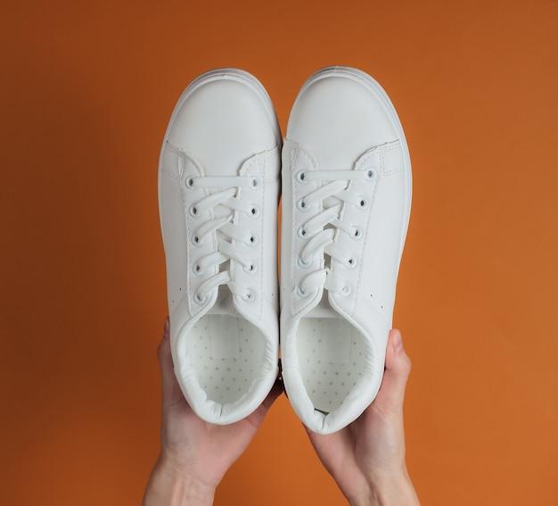 Le mani femminili tengono le scarpe da ginnastica alla moda bianche su carta marrone dello studio