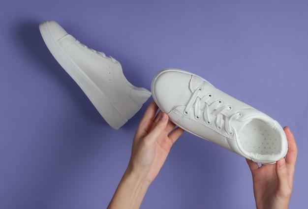 Le mani femminili tengono le scarpe da ginnastica alla moda bianche su carta viola dello studio