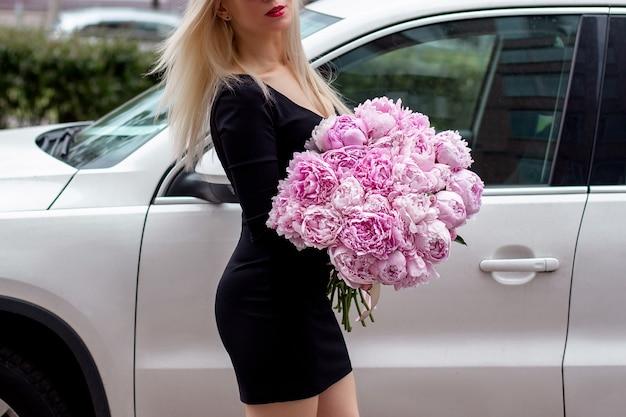 Mani femminili che tengono bel mazzo di peonie rosa