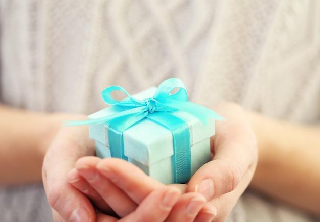 Mani femminili che tengono un bellissimo piccolo regalo avvolto con nastro di raso.
