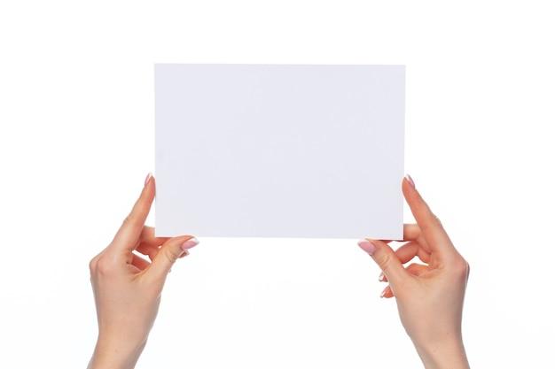Mani femminili che tengono carta bianca isolata su priorità bassa bianca