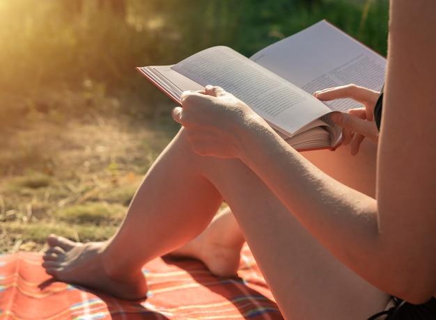 Mani femminili che tengono un libro per leggere sulla letteratura delle vacanze estive su plaid nel parco in natura