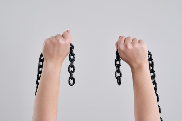 Mani femminili che tengono una catena rotta del metallo sopra la parete grigia con lo spazio della copia