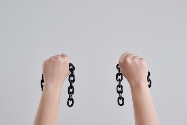 Mani femminili che tengono le catene di metallo rotte