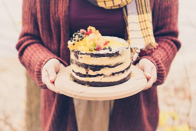 Mani femminili che tengono una torta marrone
