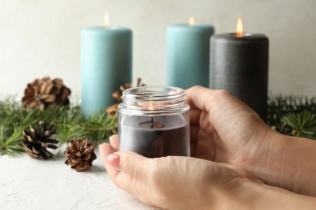 Mani femminili che tengono candela profumata accesa in un barattolo di vetro