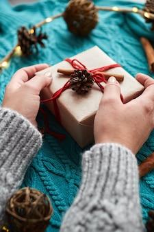 Mani femminili che tengono il contenitore di regalo di natale contro calzini rossi, un maglione lavorato a maglia blu e una ghirlanda con coni