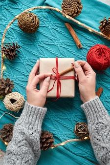 Mani femminili che tengono scatola regalo di natale e calzini rossi, un maglione lavorato a maglia blu e una ghirlanda con coni. vista dall'alto. composizione centrale