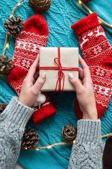 Mani femminili che tengono scatola regalo di natale e calzini rossi, un maglione lavorato a maglia blu e una ghirlanda con coni. vista dall'alto