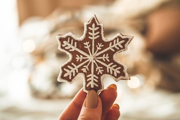 Mani femminili che tengono fiocco di neve a forma di biscotto
