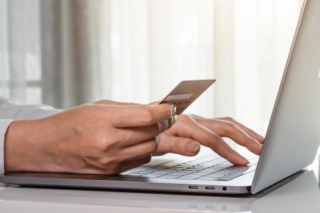 Mani femminili che tengono una carta di credito per effettuare il pagamento in linea con il computer portatile
