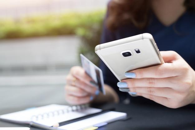 Mani femminili che tengono la carta di credito e usano il telefono.
