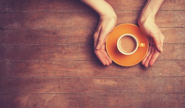Mani femminili che tengono tazza di caffè