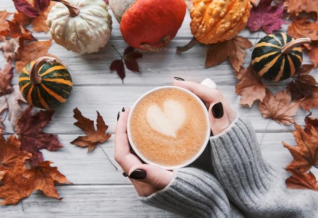 Mani femminili che tengono una tazza di caffè caldo, piatto autunnale con foglie gialle e zucche