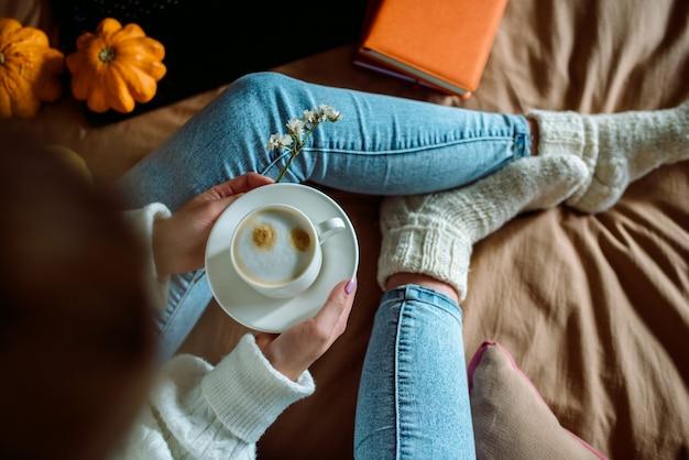 Mani femminili che tengono una tazza di tè o caffè caldo
