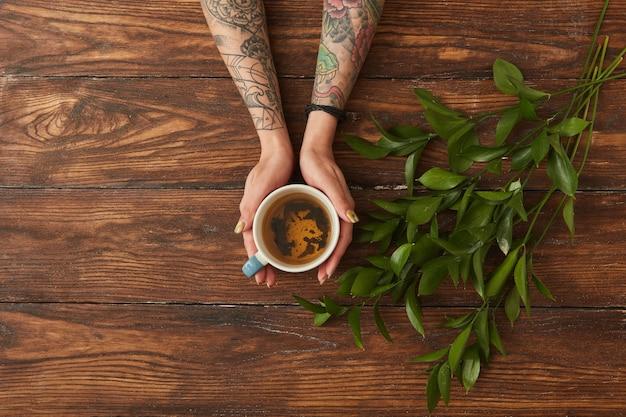 Mani femminili che tengono tazza di tè caldo
